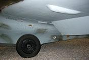 Fahrwerk und eingefahrene Landekufe sowie ausgefahrene Landeklappe und Abdeckung der Treibstoffleitung unter der Tragfläche