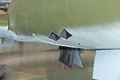 Hülsenauswurföffnungen der rechten Mk108-Bordmaschinenkanonen vor den Restabdeckungen der Hauptfahrwerksbeine
