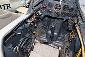 Trimmräder links neben dem Flugzeugführersitz; an der rechten Cockpitseitenwand verläuft die gelbfarbene Treibstoffleitung