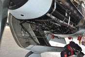 Schmierstoffkühler, Arbeitszylinder zur Steuerung der Kühlerklappe und Schlauchleitungen im unteren Haubenteil